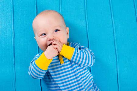 青いニット毛布にかわいい赤ちゃん。歯が生える幼児カラフルなおもちゃで遊んで。お昼寝後ベッドの少年。寝具・保育園と幼児の繊維。子供パジ