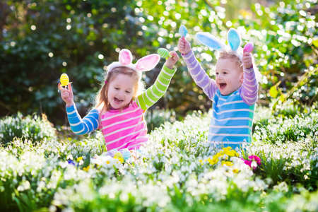 boy beautiful: Kids on Easter egg hunt in blooming spring garden. Children with bunny ears searching for colorful eggs in snow drop flower meadow. Toddler boy and preschooler girl in rabbit costume play outdoors.