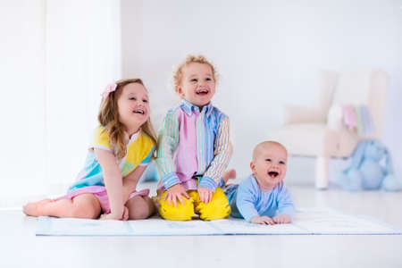 화이트 침실에서 재생 세 아이의 그룹입니다. 아이들은 집에서 재생할 수 있습니다. 보육에 취학 소녀, 유아 소년과 아기. 행복한 작은 형제와 함께 재미 자매 결합. 형제 사랑.