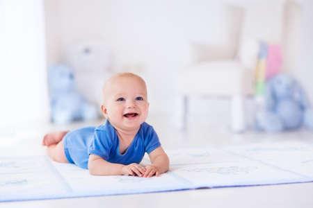 白い日当たりの良い寝室で愛らしい男の子。生まれたばかりの子供は敷物でリラックス。若い子供は保育園。家具、織物、そして子供のための寝具