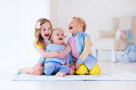 boy room: Group of three kids playing in a white bedroom. Children play at home. Preschooler girl, toddler boy and baby in nursery. Happy little brothers and sister bonding having fun together. Siblings love.