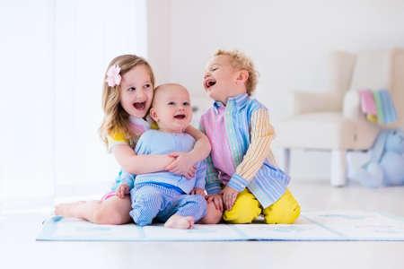 gemelos niÑo y niÑa: Grupo de tres niños jugando en una habitación blanca. Los niños juegan en casa. niña de edad preescolar, muchacho niño y el bebé en la guardería. hermanos pequeños felices y unión hermana que se divierten juntos. Los hermanos aman. Foto de archivo