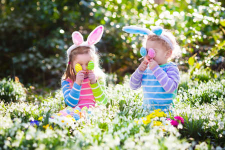 Kids on Easter egg hunt in blooming spring garden. Children with bunny ears searching for colorful eggs in snow drop flower meadow. Toddler boy and preschooler girl in rabbit costume play outdoors.