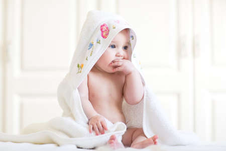persona feliz: Bebé adorable que se sienta debajo de una toalla con capucha después del baño Foto de archivo