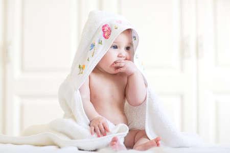 Entzückendes Baby unter einem Handtuch mit Kapuze sitzt nach dem Bad