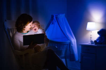 reading lamp: Mother and baby reading a book in dark bedroom. Mom and child read books before bed time. Family in the evening. Kids room interior with night lamp and bassinet. Parent holding infant next to crib.