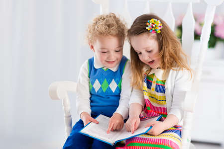 early childhood: Kids read a book. Children reading books in white chair. Toddler kid and preschooler child doing homework. Little boy and girl study at home after kindergarten. Brother and sister play and laugh.