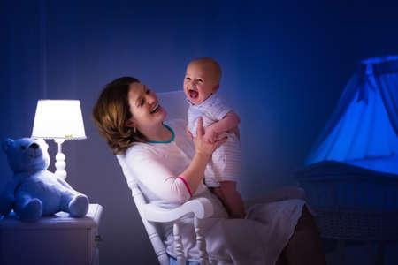 Mutter und Kind ein Buch in dunklen Schlafzimmer zu lesen. Mama und Kind lesen Bücher vor dem Schlafengehen. Familie am Abend. Kinderzimmer Interieur mit Nachtlampe und bassinet. Eltern halten Säugling neben Krippe. Standard-Bild