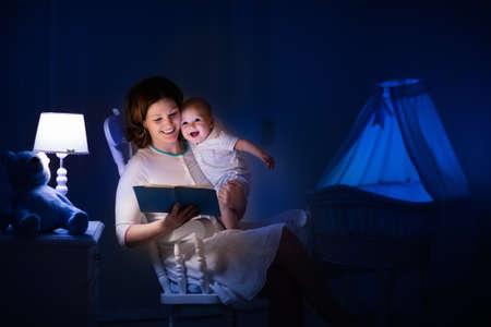 Moeder en baby het lezen van een boek in een donkere kamer. Moeder en kind boeken lezen vóór het slapen gaan. Familie in de avond. Kids kamer interieur met nachtlampje en wieg. Moederholding baby naast wieg.