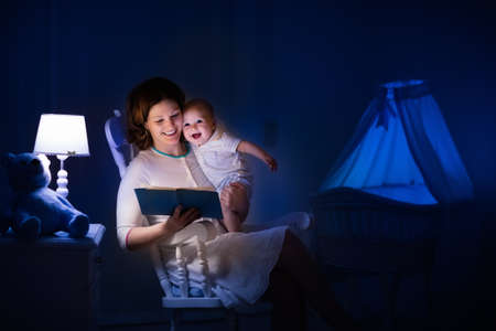 light in dark: Mother and baby reading a book in dark bedroom. Mom and child read books before bed time. Family in the evening. Kids room interior with night lamp and bassinet. Parent holding infant next to crib.