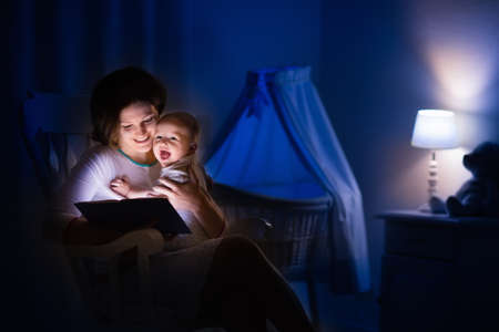 bassinet: Mother and baby reading a book in dark bedroom. Mom and child read books before bed time. Family in the evening. Kids room interior with night lamp and bassinet. Parent holding infant next to crib.