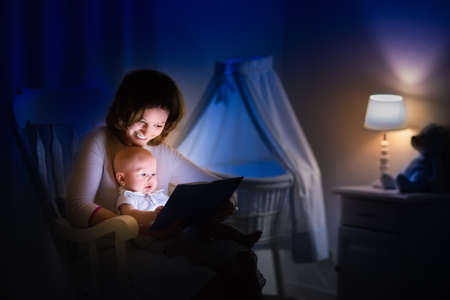 Mother and baby reading a book in dark bedroom. Mom and child read books before bed time. Family in the evening. Kids room interior with night lamp and bassinet. Parent holding infant next to crib.