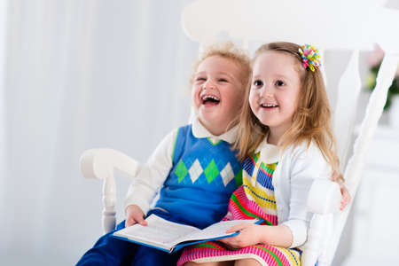 early education: Kids read a book. Children reading books in white chair. Toddler kid and preschooler child doing homework. Little boy and girl study at home after kindergarten. Brother and sister play and laugh.