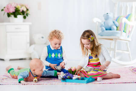 baby playing: Kids play at home. Children playing in white sunny nursery. Little girl having fun at doll tea party with her brothers. Siblings making lunch for toy bear. Toddler, preschooler and baby at day care.
