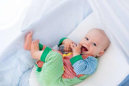 Bebé divertido en pijamas de colores con la botella de agua potable o leche en cuna blanca con dosel. la nutrición saludable para los niños. Interior del cuarto de niños y ropa de cama para bebés. Los niños beben fórmula en la cama.