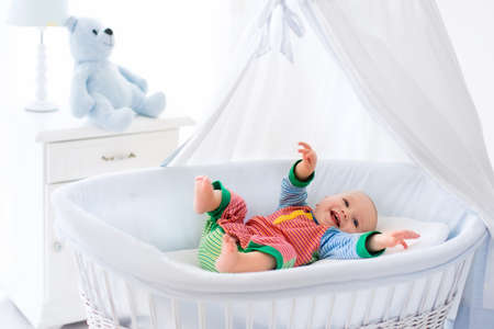Funny baby in white crib with canopy. Nursery interior and bedding for kids. Laughing little boy playing in moses basket. Bedroom with bassinet for young children. Happy child in colorful pajamas.