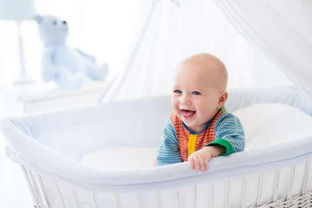 Grappige baby in witte wieg met baldakijn. Nursery inter en beddengoed voor kinderen. Lachend weinig jongen die in Mozes mand. Slaapkamer met wieg voor jonge kinderen. Gelukkig kind in kleurrijke pyjama. Stockfoto