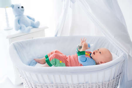 bassinet: Funny baby in colorful pajamas with bottle drinking water or milk in white crib with canopy. Healthy nutrition for kids. Nursery interior and bedding for infant. Children drink formula in bed.