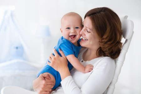 lactancia materna: Joven madre sosteniendo a su hijo recién nacido. Bebé lactante mamá. La mujer y el muchacho recién nacido en el dormitorio blanco con mecedora y azul cuna. Vivero interior. Madre que juega con niño riendo. Familia en el país Foto de archivo