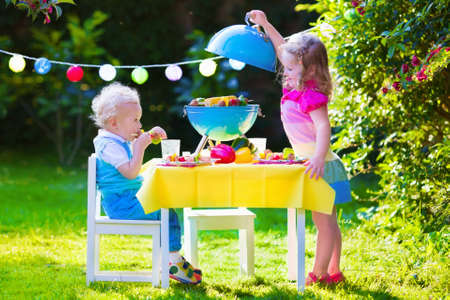 meal: Children grilling meat. Family camping and enjoying BBQ. Brother and sister at barbecue preparing steaks and sausages. Kids eating grill and healthy vegetable meal outdoors. Garden party for child. Stock Photo