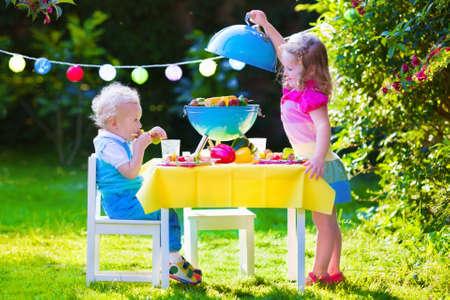 saucisse: Enfants griller la viande. Camping familial et barbecue profiter. Fr�re et soeur au barbecue pr�parer des steaks et saucisses. Enfants manger gril et repas du l�gume sain ext�rieur. Garden party pour les enfants.