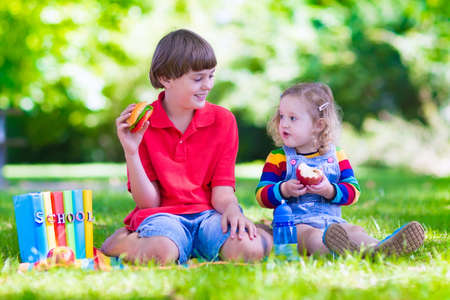 school yard: Children in school yard. Happy laughing teenager student boy and preschool girl in the school garden reading books and having apple for healthy snack, back to school concept