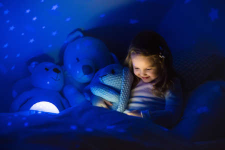 light to dark: Little girl reading a book in bed. Dark bedroom with night light projecting stars on room ceiling. Kids nursery and bedding. Children read before bedtime. Toddler child playing with lamp and bear toy.