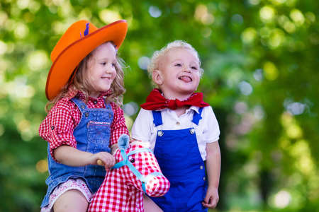 babies playing: Little boy and girl dressed up as cowboy and cowgirl playing with toy rocking horse in park. Kids play outdoors. Children in Halloween costumes at trick or treat. Toys for preschooler or toddler child Stock Photo