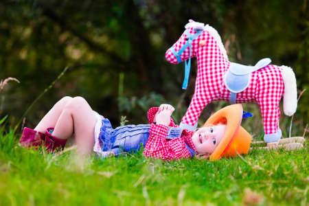 어린 소녀 카우걸 장난감 락 말 공원에서 놀고로 꾸몄다. 어린이 카우보이 야외에서 재생할 수 있습니다. 할로윈 의상에서 어린이 트릭이나 치료. 미