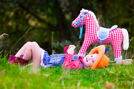 Little girl dressed up as cowgirl playing with toy rocking horse in park. Kids play cowboy outdoors. Children in Halloween costumes at trick or treat. Toys for preschooler kid or toddler child.