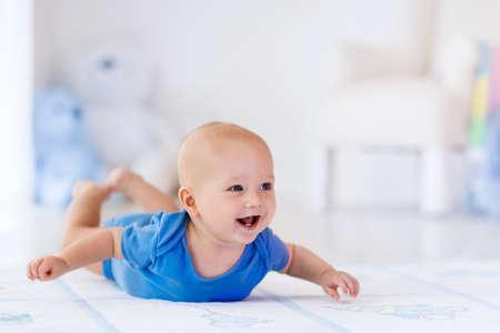 Adorable petit garçon en blanc chambre ensoleillée. enfant nouveau-né de détente sur un tapis. Garderie pour les jeunes enfants. Meubles, textiles et de la literie pour les enfants. Nouveau gosse né pendant le temps de ventre avec des jouets à une fenêtre. Banque d'images - 54637330