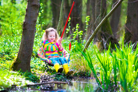 catches: Child playing outdoors. Preschooler kid catching fish with red rod. Little girl fishing in forest river in summer. Adventure kindergarten day trip in wild nature, explorer hiking and watching animals. Stock Photo