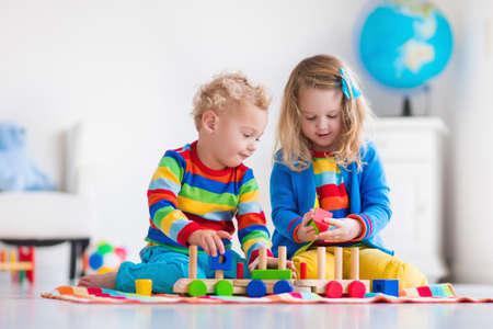 Kinder spielen mit Holzeisenbahn. Kleinkind Kind und Baby spielen mit Blöcken, Zügen und Autos. Pädagogische Spielwaren für Kinder im Vorschul und Kindergartenkind. Junge und Mädchen bauen Spielzeug-Eisenbahn zu Hause oder Kindertagesstätte.