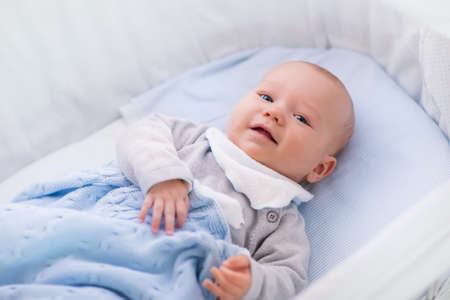 awake: Newborn baby boy in bed. New born child sleeping under a white knitted blanket. Children sleep. Bedding for kids. Infant napping in bed. Healthy little kid shortly after birth. Cable knit textile.