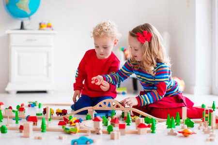wood blocks: Children playing with wooden train. Toddler kid and baby play with blocks, trains and cars. Educational toys for preschool and kindergarten child. Boy and girl build toy railroad at home or daycare.