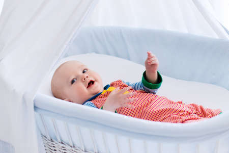 bassinet: Funny baby in white crib with canopy. Nursery interior and bedding for kids. Laughing little boy playing in moses basket. Bedroom with bassinet for young children. Happy child in colorful pajamas.
