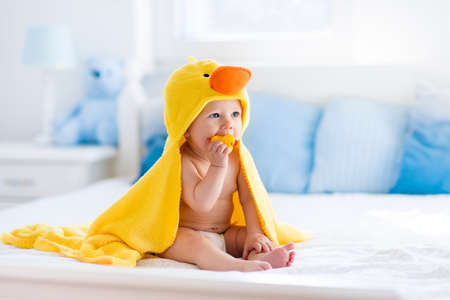 �infant: Happy laughing baby wearing yellow hooded duck towel sitting on parents bed after bath or shower. Clean dry child in bedroom. Bathing and washing of little kids. Children hygiene. Textile for infants.