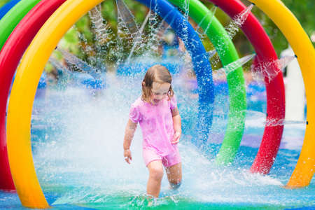 aquapark: Happy little toddler girl running through a fountain having fun with water splashes in a swimming pool enjoying day trip to an aqua amusement park during summer family vacation Stock Photo