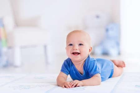 guardera: Beb� adorable en blanco soleado dormitorio. ni�o reci�n nacido se relaja en una alfombra. Guarder�a para ni�os peque�os. Muebles, textiles y ropa de cama para los ni�os. Nuevo ni�o nacido durante el tiempo boca abajo con los juguetes en una ventana.