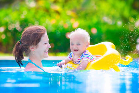 early summer: Happy family, young active mother and adorable curly little baby having fun in a swimming pool, child learning to swim in an inflatable toy ring, enjoying summer vacation at a tropical resort