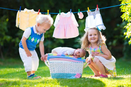 child bath: Newborn child on a pile of clean dry towels. Brother and sister kissing little sibling. Siblings bonding. Kids and baby clothing on laundry line and basket. Children playing outdoors in summer garden