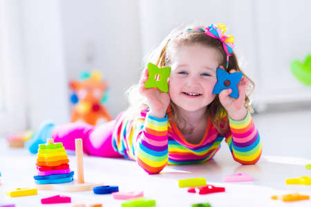 day care: Child playing with wooden toys at preschool. Cute toddler girl having fun with toy blocks, building a tower at home or day care. Educational kids toy for nursery or kindergarten.
