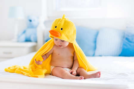 child bath: Happy laughing baby wearing yellow hooded duck towel sitting on parents bed after bath or shower. Clean dry child in bedroom. Bathing and washing of little kids. Children hygiene. Textile for infants.