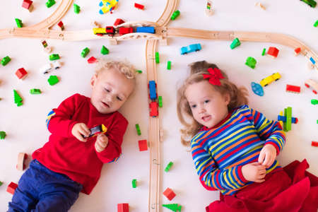 two children: Children playing with wooden train. Toy railroad. Toddler kid and baby play with blocks, trains and cars. Educational toys for preschool and kindergarten child. View from above, kids on the floor.