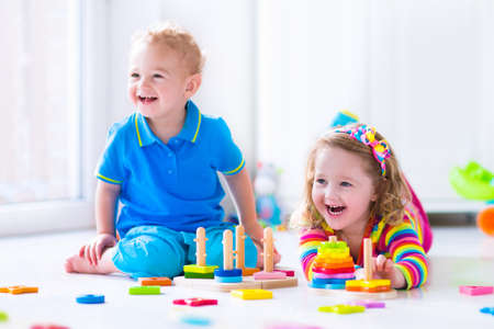 baby toys: Kids playing with wooden toys. Two children, cute toddler girl and funny baby boy, playing with toy blocks, building towers at home or day care. Educational child toys for preschool and kindergarten.