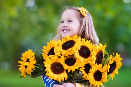 Sun flower: Glückliches lachendes kleines Mädchen mit Sonnenblumen Bouquet. Kind spielt mit Sonnenblumen. Kinder, die frische Sonnenblumen im Garten. Kinder im Sommer im Garten. Outdoor-Spaß für Familien. Lizenzfreie Bilder