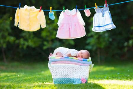 detersivi: Neonato su una pila di asciugamani puliti e asciutti. Nuovo bambino nato dopo il bagno in un asciugamano. Lavare i vestiti familiari. Capretti portano appeso su una linea all'aperto nel giardino estivo. Abbigliamento infantile, tessile per i bambini.