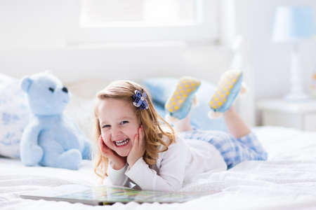 joy of reading: Funny happy toddler girl reading a book and playing with her toy teddy bear in bed. Kids play at home. White nursery. Child in sunny bedroom. Children read and study. Interior for baby and young kid.
