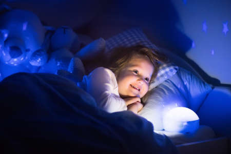 teddybear: Little girl reading a book in bed. Dark bedroom with night light projecting stars on room ceiling. Kids nursery and bedding. Children read before bedtime. Toddler child playing with lamp and bear toy.