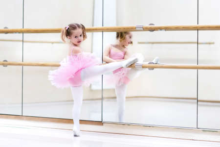 ballerina tights: Little ballerina girl in a pink tutu. Adorable child dancing classical ballet in a white studio. Children dance. Kids performing. Young gifted dancer in a class. Preschool kid taking art lessons.